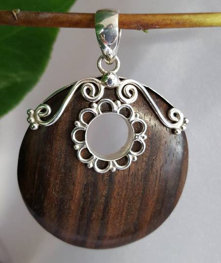 Polished wooden pendant with silver detailing