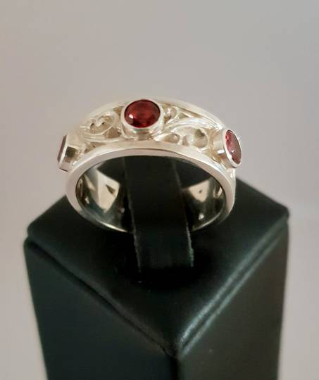 Silver and garnet ring with koru scrolls
