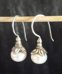 Cupped pearl earrings set in silver flowers