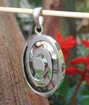 Paua shell pendant with spiralling silver koru