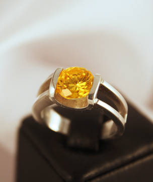 Silver ring with cupped tension set yellow stone